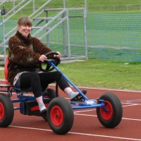 Female participant smiling while riding a go-kart